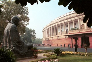 14 Dec 2001, New Delhi, India --- Seven civilians and five terrorists were killed in a suicide attack on the Indian Parliament.  The statue of the apostle of peace, Mahatma Gandhi, looks on the Parliament building. --- Photo by Pallava Bagla/Corbis Sygma --- Image by © Pallava Bagla/Corbis
