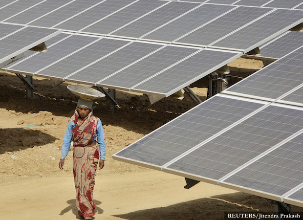 A worker walks through the installed solar modules at Naini solar power plant in Allahabad