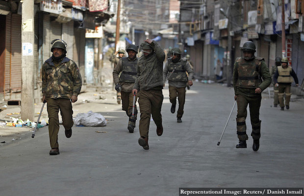 Indian police chase away activists from JKLF during a curfew in Srinagar