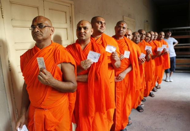 Hindu saints stand in line to cast their votes at a polling station in Ahmedabad