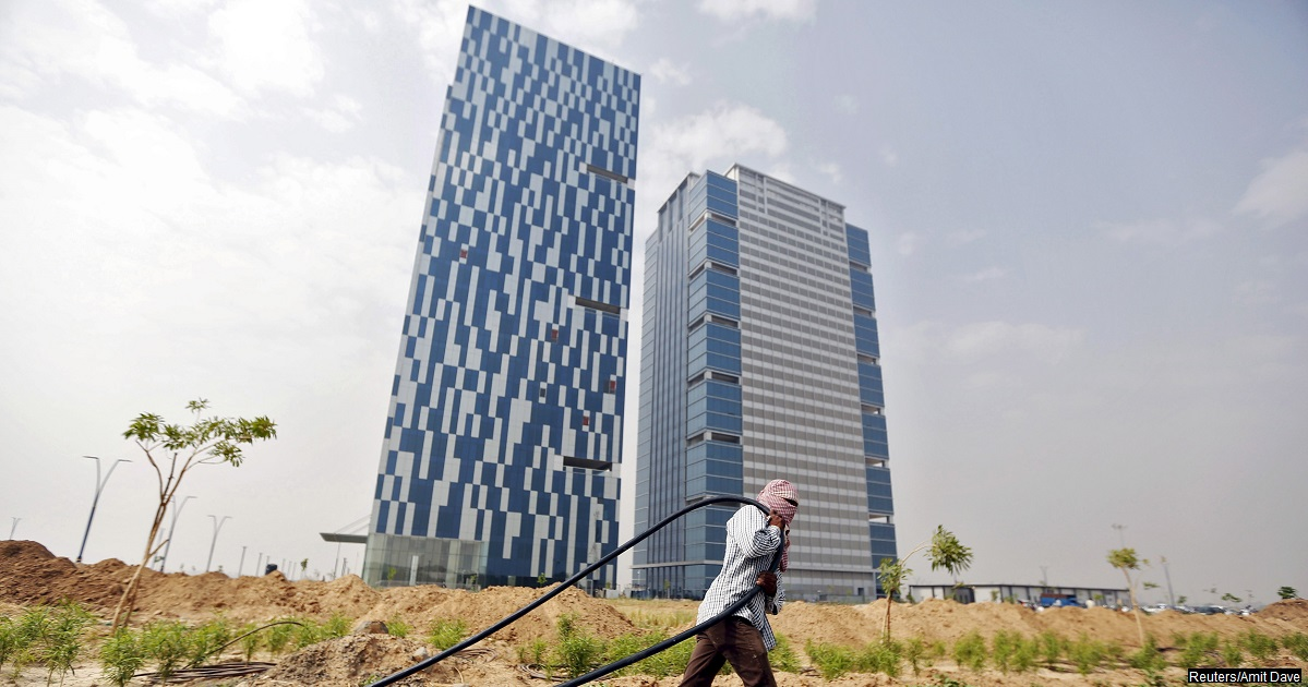 "A labourer pulls a cable in front of two office buildings in Gujarat International Finance Tec-City (GIFT) at Gandhinagar, in the western Indian state of Gujarat, April 10, 2015. India's push to accommodate a booming urban population and attract investment rests in large part with dozens of ""smart"" cities like the one being built on the dusty banks of the Sabarmati river in western India. Picture taken April 10, 2015.  REUTERS/Amit Dave  - RTR4XCPJ"
