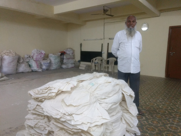 Mannan Siddiqui with gray fabric produced in his factory.